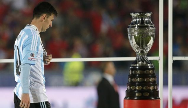 Argentina's Lionel Messi walks with his silver medal past the Copa America trophy during the presentation ceremony after Chile defeated his team in the Copa America 2015 final soccer match at the National Stadium in Santiago, Chile, July 4, 2015. REUTERS/Ivan Alvarado